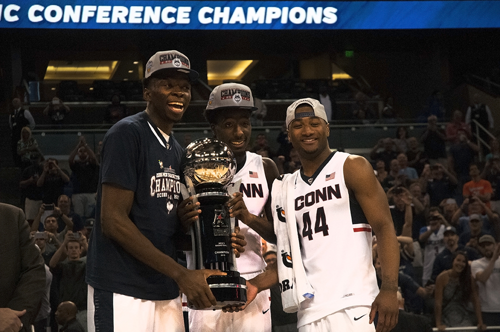 From left, AMida Brimah, Daniel Hamilton and Rodney Purvis pose with American Athletic Conference tournament trophy following UConn's victory over Memphis at the Amway Center on Sunday March 13, 2016. The Huskies three day run in Orlando was a memorable moment this season. (Ashley Maher/The Daily Campus)