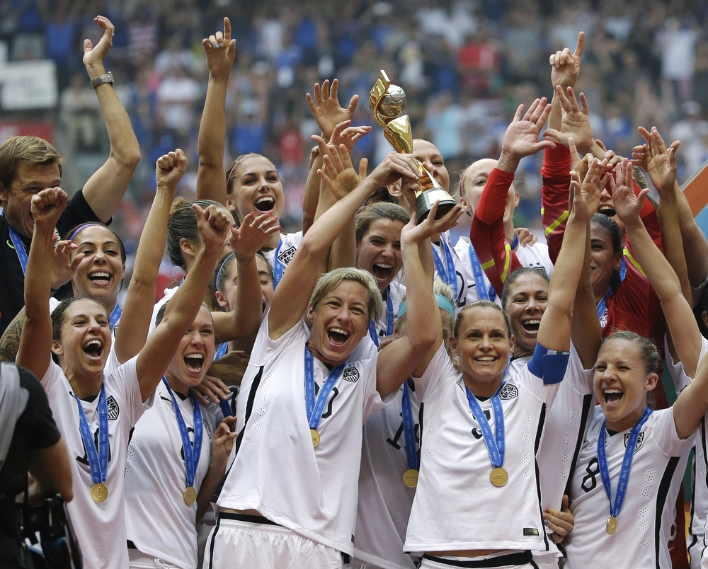 In this July 5, 2015, file photo, the United States Women's National Team celebrates with the trophy after they beat Japan 5-2 in the FIFA Women's World Cup soccer championship in Vancouver, British Columbia, Canada. Five players from the World Cup-winning U.S. national team have accused the U.S. Soccer Federation of wage discrimination in an action filed with the Equal Employment Opportunity Commission. (AP Photo/Elaine Thompson, File)