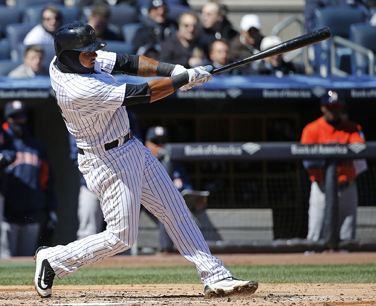 New York Yankees shortstop Starlin Castro (14) hits a two-run double off Houston Astros starting pitcher Dallas Keuchel during the second inning of an opening day baseball game in New York, Tuesday, April 5, 2016. (AP Photo/Kathy Willens)
