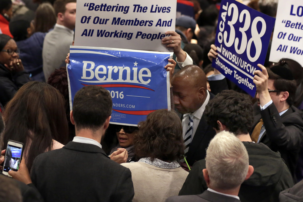 A Bernie Sanders supporter holds a campaign sign as she's escorted from a rally of Democratic presidential candidate Hillary Clinton and New York Gov. Andrew Cuomo at the Javits Convention Center, Monday, April 4, 2016 in New York. Cuomo signed a law that will gradually raise New York's minimum wage to $15. (AP Photo/Richard Drew)