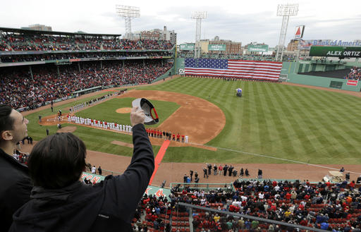 Fans cheer and wave at the conclusion of the singing of the national anthem before the home opener baseball game between the Boston Red Sox and the Baltimore Orioles at Fenway Park, Monday, April 11, 2016, in Boston. (AP Photo/Steven Senne)