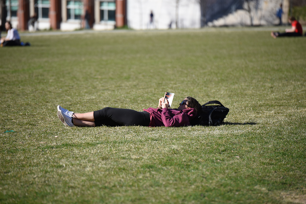 A student is laying on the grass behind the student union and reading a book at April 20th, warm day at UConn. (Zhelun Lang/The Daily Campus)