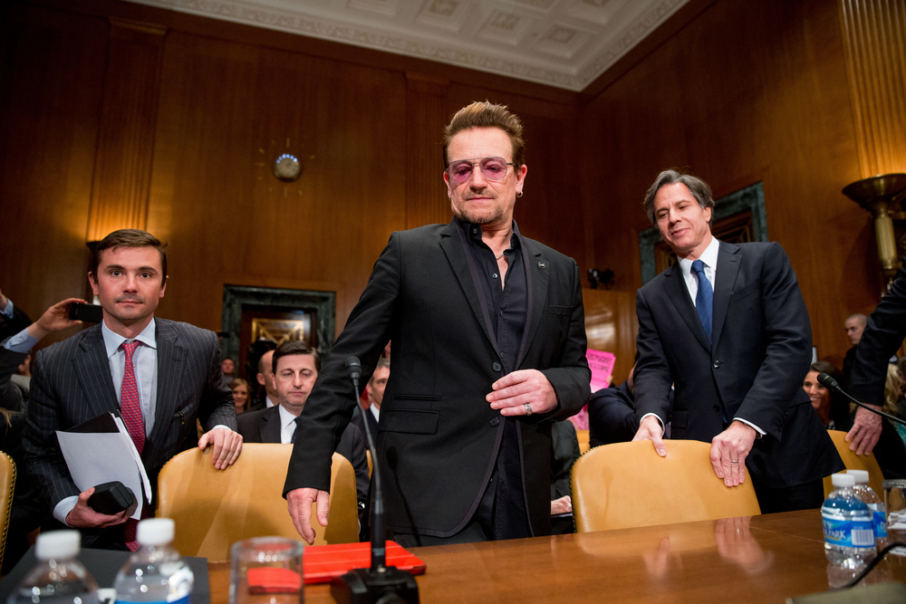 Irish rock star and activist Bono, center, followed by Deputy Secretary of State Tony Blinken, right, arrives on Capitol Hill in Washington, Tuesday, April 12, 2016, to testify before the Senate State, Foreign Operations, and Related Programs subcommittee hearing on the causes and consequences of violent extremists, and the role of foreign assistance. (AP Photo/Andrew Harnik)