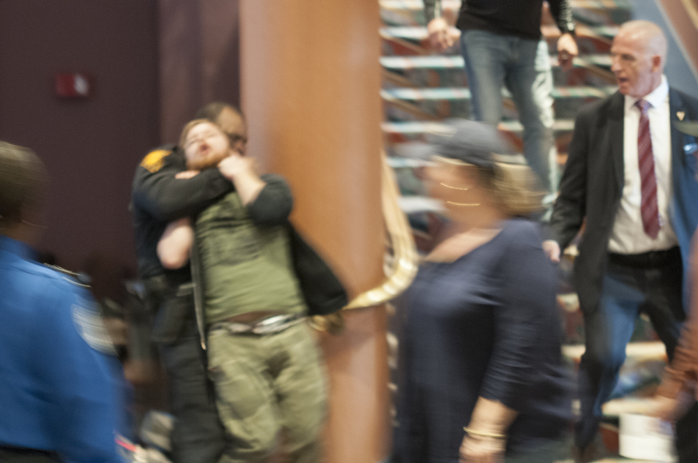 A police officer removes a protester from Republican presidential candidate Donald Trump's rally in Bridgeport on Saturday, April 23, 2016. The man tried to run back into the crowd after initially being removed. The officer was able to stop the man by placing him in a chokehold and dragging him out of the building. (Kyle Constable/The Daily Campus)