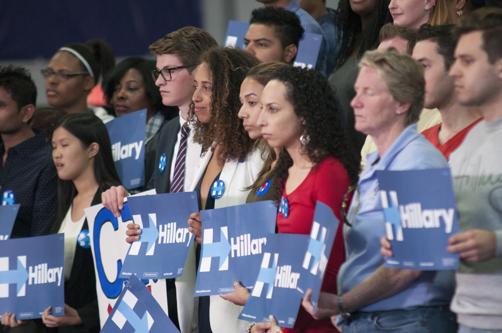 Supporters of Democratic presidential candidate Hillary Clinton lined up behind her on a separate stage during a campaign rally at the University of Bridgeport on Sunday, April 24, 2016. (Kyle Constable/The Daily Campus)