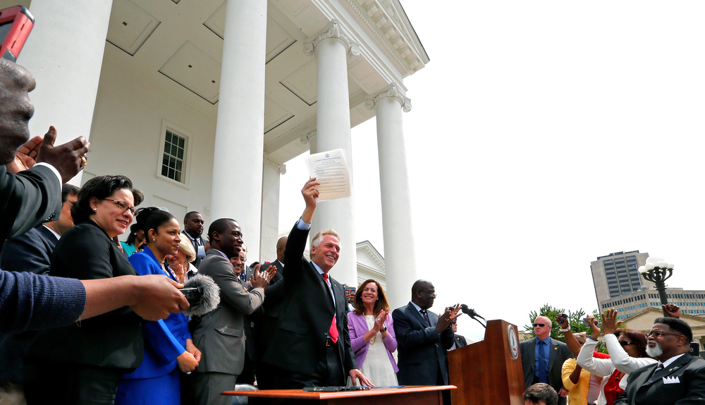 Gov. Terry McAuliffe holds up the order he signed to restore rights to felons in Virginia at the Capitol in Richmond, Va., Friday, April 22, 2016. More than 200,000 convicted felons will be able to cast ballots in the swing state of Virginia in November's election under a sweeping executive order by McAuliffe announced Friday that restores their rights to vote and run for office. (Mark Gormus /Richmond Times-Dispatch via AP)