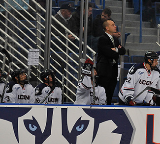 Mike Cavanaugh stands over the bench during a UConn game. (Amar Batra/The Daily Campus)