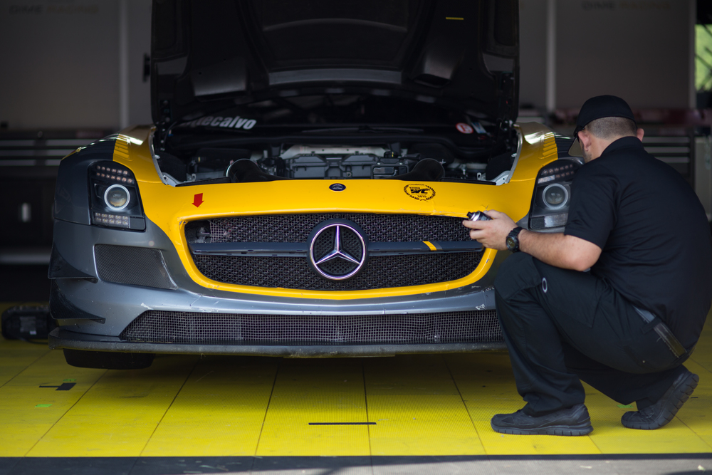 A team mechanic polishes a Mercedes SLS AMG GT3 in the paddock. (Jackson Haigis/Daily Campus)