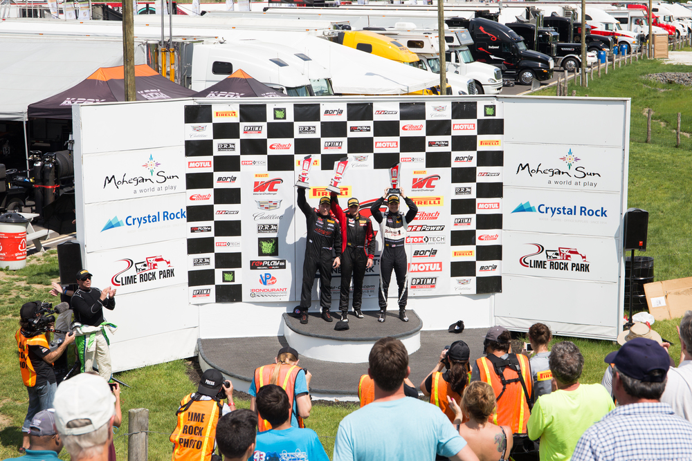 The top three drivers from the GTS race stand atop the podium. The cars are separated into categories based on several factors, including size, horsepower, and more. (Jackson Haigis/Daily Campus)