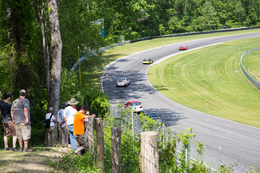 Spectators enjoy the shade and watch the Touring cars descend the downhill section of the track. There are over a dozen different places from which to watch the race, meaning that spectators can get many different perspectives of the track throughout the day. (Jackson Haigis/Daily Campus)