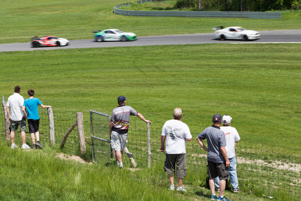 Spectators catch a view of the cars towards the beginning of the track. Many fans camp out for the weekend, and car enthusiasts from across the Northeast gather for the event.(Jackson Haigis/Daily Campus)