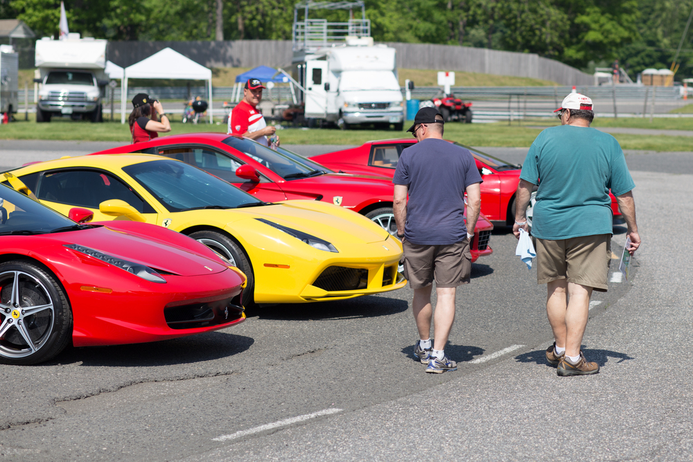 Also in the center of the track is a parking area with areas reserved for various car clubs. Here a few fans check out the Ferraris located in Miller Motorcars' area. (Jackson Haigis/Daily Campus)