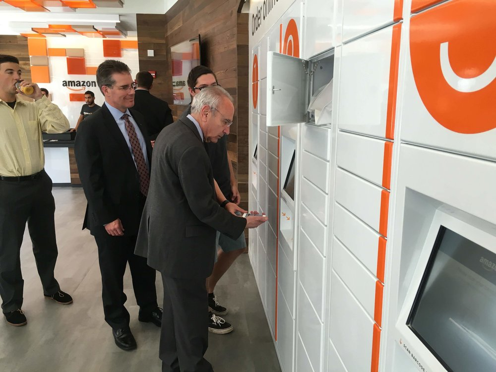 Amazon@Storrs campus associate Kasey Pekala (right) gives Mansfield mayor Paul Shapiro (front) a tutorial in using the Amazon@Storrs kiosk. (Chris McDermott/Daily Campus)