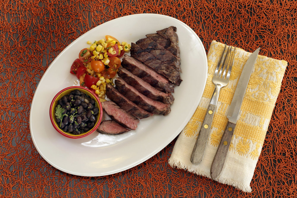 This Aug. 4, 2016 photo shows skirt steak with beer-braised black beans and corn salsa, styled by Sarah Abrams, displayed at the Institute of Culinary Education in New York. This dish is from a recipe by Elizabeth Karmel. (Richard Drew/AP)