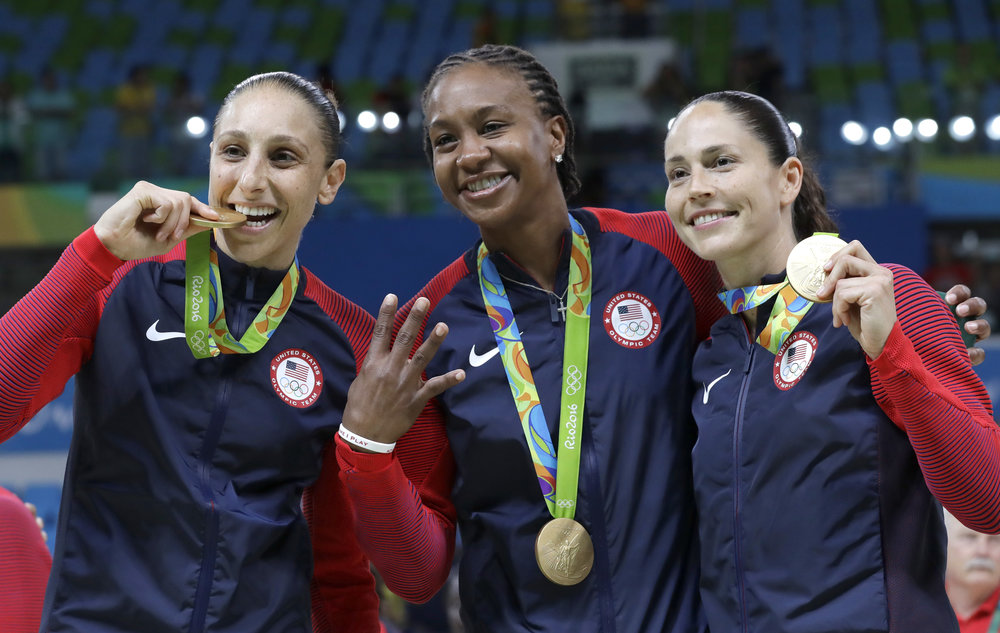 United States' Diana Taurasi, left, Tamika Catchings, center, and Sue Bird, right, celebrate with their gold medals after their win in a women's basketball game against Spain at the 2016 Summer Olympics in Rio de Janeiro, Brazil, Saturday, Aug. 20, 2016.  Taurasi and Bird are UConn alums. (Eric Gay/AP)