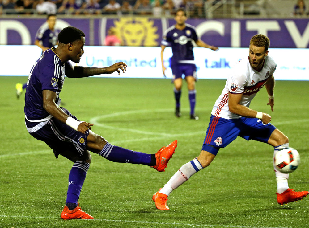 Orlando City's Cyle Larin, left, takes a shot on goal past Toronto FC's Josh Williams during the second half of an MLS soccer game, Wednesday, Aug. 24, 2016, in Orlando, Fla. Toronto FC won 2-1. (John Raoux/AP)