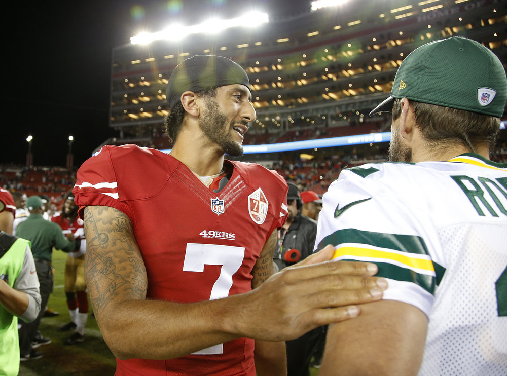 San Francisco 49ers quarterback Colin Kaepernick, left, greets Green Bay Packers quarterback Aaron Rodgers at the end of an NFL preseason football game Friday, Aug. 26, 2016, in Santa Clara, Calif. Green Bay won 21-10. (Tony Avelar/AP)