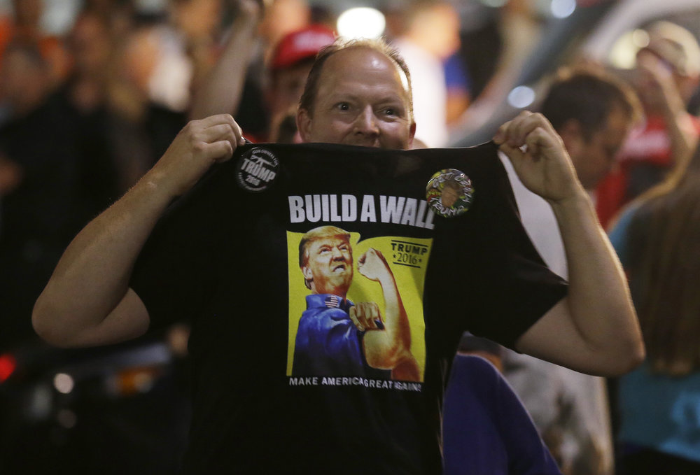 "A supporter of Republican presidential candidate Donald Trump holds up his shirt, which bears the Trump slogan ""Build a Wall,"" following a rally for Trump, Tuesday, Aug. 30, 2016, in Everett, Wash. (Ted S. Warren/AP)"