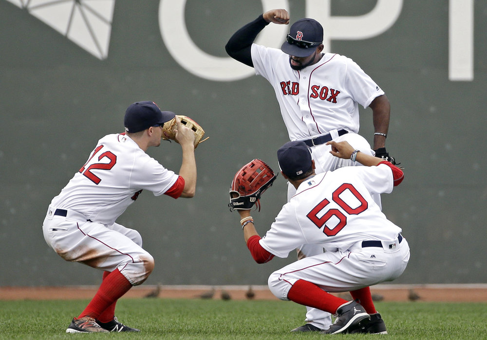Boston   Red   Sox  outfielders Brock Holt (12), Mookie Betts (50) and Jackie Bradley Jr., top, celebrate after defeating the Tampa Bay Rays 8-6 in a baseball game at Fenway Park, Wednesday, Aug. 31, 2016, in  Boston . (Elise Amendola/AP)