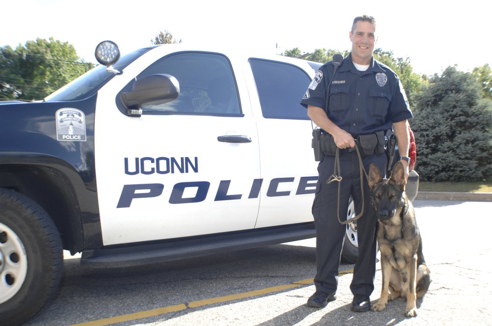 UConn Police Department (UCPD) implemented body cameras on July 1, 2016. Here an officer stands with a K9 member of the force outside of the police department on North Eagleville Road. (File Photo/The Daily Campus)