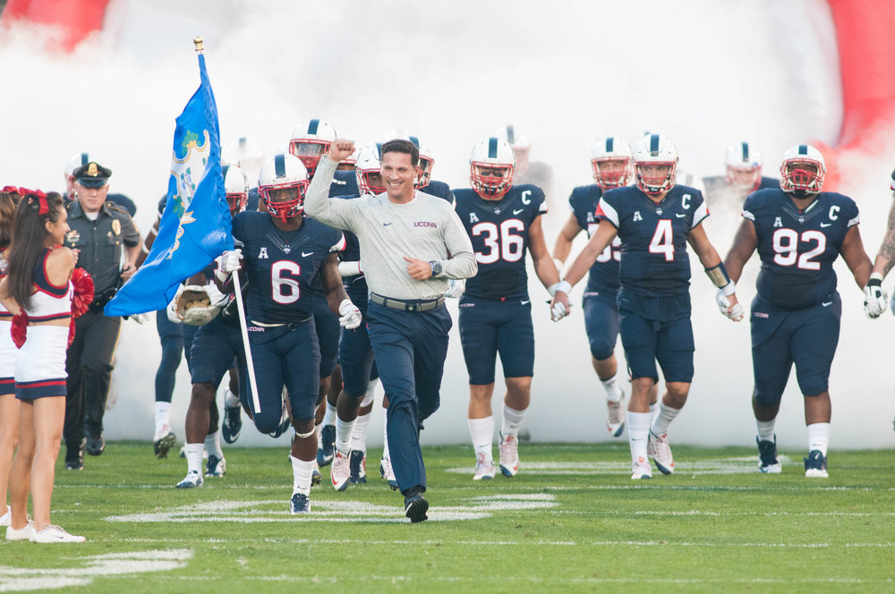 UConn head coach Bob Diaco leads his team out of the tunnel in their season opener against Maine at Pratt & Whitney Stadium at Rentschler Field. (Jackson Haigis/The Daily Campus)