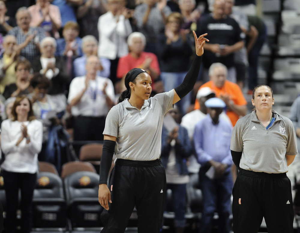 Minnesota Lynx' Maya Moore, left, and Lindsay Whalen are acknowledged by fans for their gold medal win in the Olympics, at the start of a WNBA basketball game against the Connecticut Sun, Friday, Aug. 26, 2016, in Uncasville, Conn. (AP Photo/Jessica Hill)