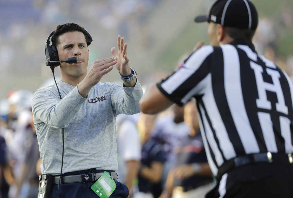 Connecticut head coach Bob Diaco, left, signals for a timeout to an official in the second half of an NCAA collegefootball game against Navy in Annapolis, Md., Saturday, Sept. 10, 2016. Navy won 28-24. (AP Photo/Patrick Semansky)