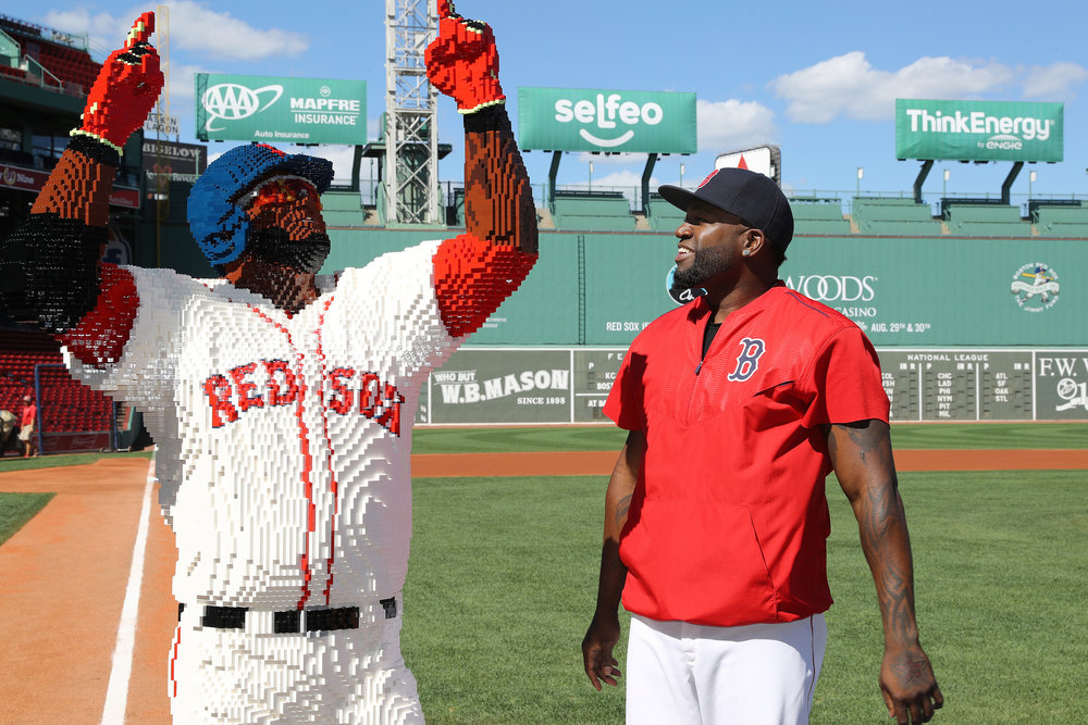 In this image released on Wednesday, Aug. 31, 2016, Boston Red Sox designated hitter David Ortiz admires the detail of his life-size LEGO likeness on home plate at Fenway Park in Boston. (Damian Strohmeyer/AP Images for LEGO® Systems, Inc.)
