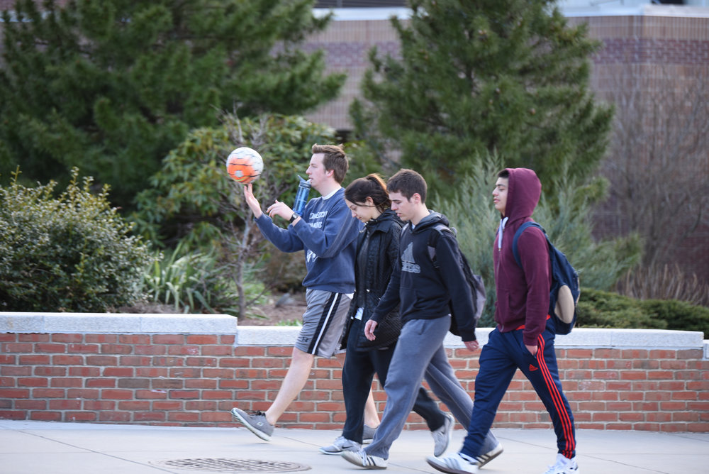 Students walk across campus with their perfectly intact backpacks, something that the author does not have. (Zhelun Lang/The Daily Campus)