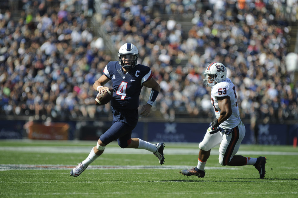 Quarterback Bryant Shirreffs runs the ball around a Virginia defender en route to a 13-10 victory on Saturday, Sept. 17 at Pratt and Whitney Stadium in East Hartford. Shirreffs passed for 154 yards and completed 13 of 24 attempts. (Photo by Jason Jiang/The Daily Campus)