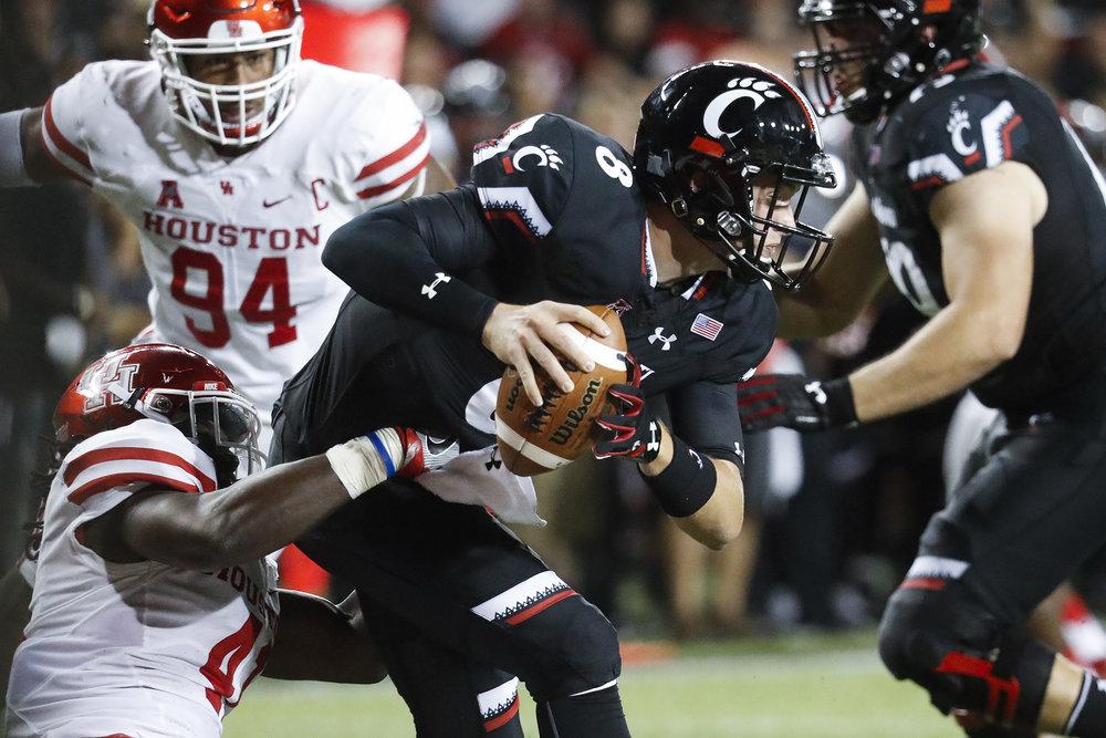 Houston linebacker Steven Taylor, left, sacks Cincinnati quarterback Hayden Moore during the second half of an NCAA college football game, Thursday, Sept. 15, 2016, in Cincinnati.Houston won 40-16. (AP/John Minchillo)
