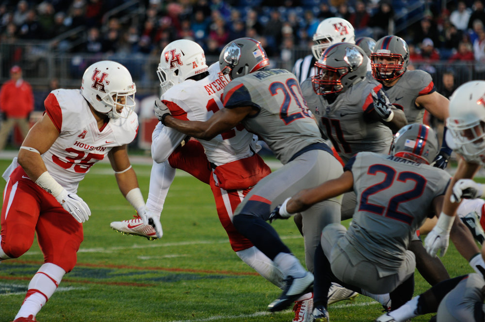 The UConn defensive line tackles a member of the University of Houston offensive line during the Huskies end of season win over the Cougars on Nov. 21, 2016. (Amar Batra/The Daily Campus)