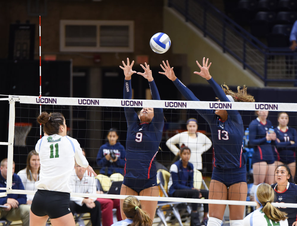 Senior outside blocker Camille Evans (9) and junior middle blocker Tosin Adeniyi (13) prepare to block a ball during the Huskies 3-1 victory over Tulane on Sunday, Sept. 22, 2016. (Zhelun Lang/The Daily Campus)