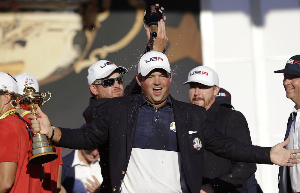 United States' Jimmy Walker and United States' Ryan Moore pour champagne on United States' Patrick Reed during the closing ceremony of the Ryder Cup golf tournament Sunday, Oct. 2, 2016, at Hazeltine National Golf Club in Chaska, Minn. (David J. Phillip/AP Photo)