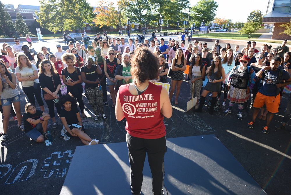 A student coordinator reads a piece to the crowd during the speakout session after the UConn Slutwalk march on Friday, Oct. 7, 2016. The speakout session is a part of the SlutWalk when anyone can take a microphone and share their experiences related to sexual assault. (Zhelun Lang/The Daily Campus)