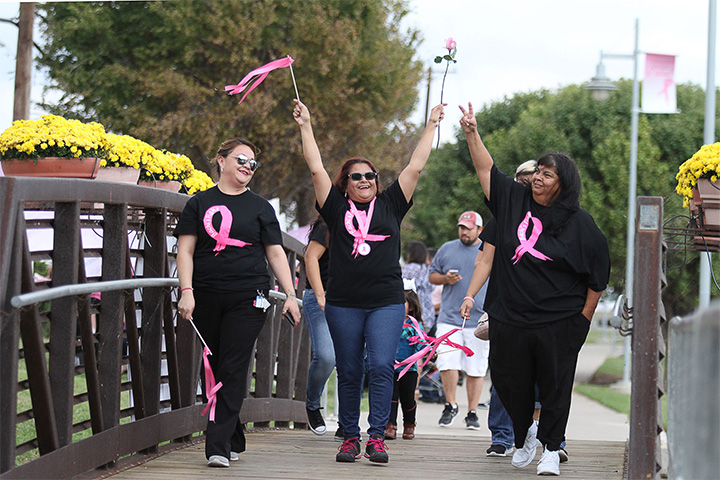 Breast cancer survivor Beatriz Madero, center, makes her victory lap around the pond with family at Pink the Park Breast Cancer Awareness event at Memorial Gardens Park Sunday, Oct.9, 2016, in Odessa, Texas. (Jacob Ford/Odessa American via AP)