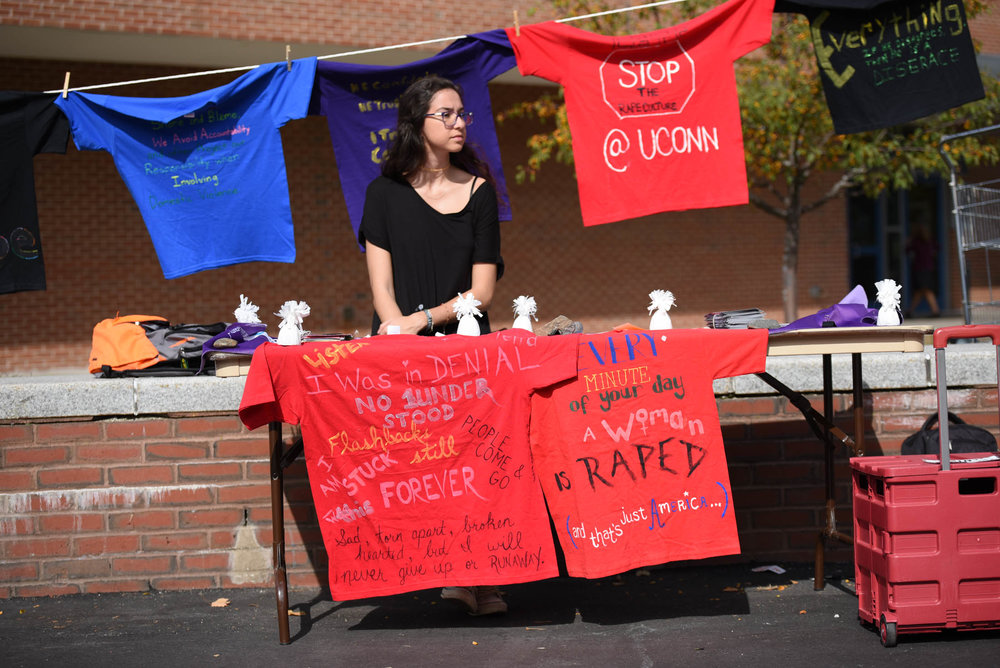 Manu Bayraktar, a junior geoscience major, volunteers for the annual Clothesline Project outside of the Student Union on Thursday, Oct. 13, 2016. Each t-shirt symbolizes the past and present experiences of a UConn student who has either suffered from sexual assault or been moved by survivors. (Zhelun Lang/The Daily Campus)