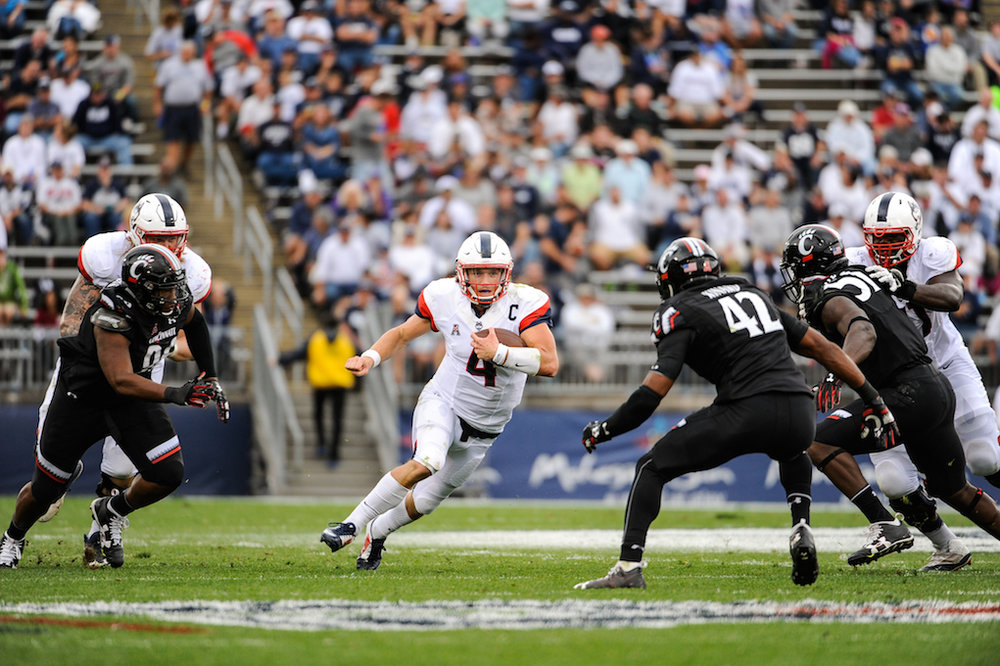 UConn junior quarterback Bryant Shirreffs (#4) scrambles to evade a tackle by UC's senior linebacker Antonio Kinard (#42). The Huskies defeated the Bearcats 20-9 on Saturday Oct. 8, 2016 at Rentschler Field at Pratt and Whitney Stadium. (Jason Jiang/The Daily Campus)