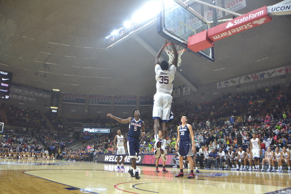 Amida Brimah (#35) gets airborne for a two-handed dunk while Daniel Hamilton (#5), Breanna Stewart (#30), Rodney Purvis (#44) and others look on during last year's First Night at Gampel Pavilion. (Bailey Wright/The Daily Campus)