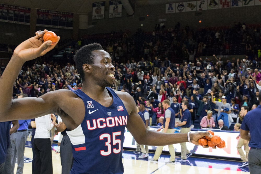 Senior center Amida Brimah throws out prizes to the crowd at the conclusion of First Night on Friday, Oct. 14 at Gampel Pavilion. A captain for his third straight season, Brimah impressed in the scrimmage, draining eight points and grabbing three rebounds. (Jackson Haigis/The Daily Campus)