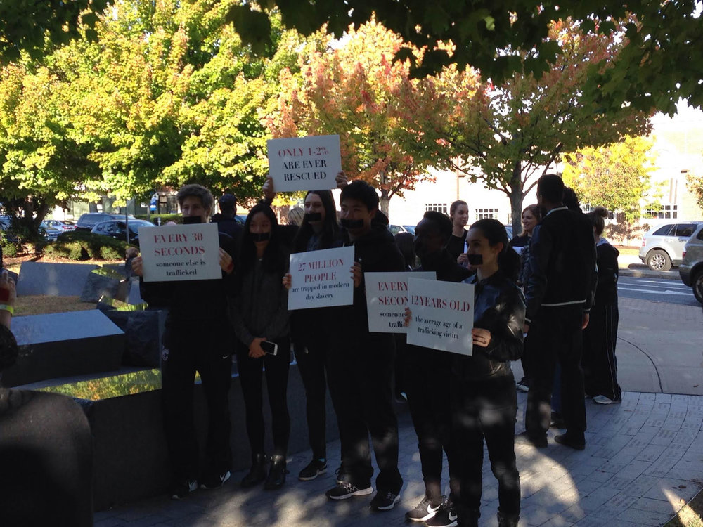 Students and community members held up posters with human trafficking statistics to inform individuals in West Hatford on Saturday, Oct. 15. (Sarah Al-Arshani/The Daily Campus)