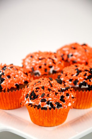 a chocolate cupcake with halloween colored sprinkles in an orange foil wrapper courtesy