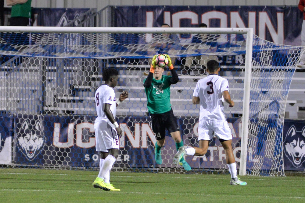 Junior goalkeeper Scott Levene saves a loose shot during the first half of the Huskeis 1-0 overtime shutout against Boston College on Tuesday, Oct. 18, 2016 at Morrone Stadium. Levene helped direct the Huskies attacks throughout the entire game. (Amar Batra/The Daily Campus)