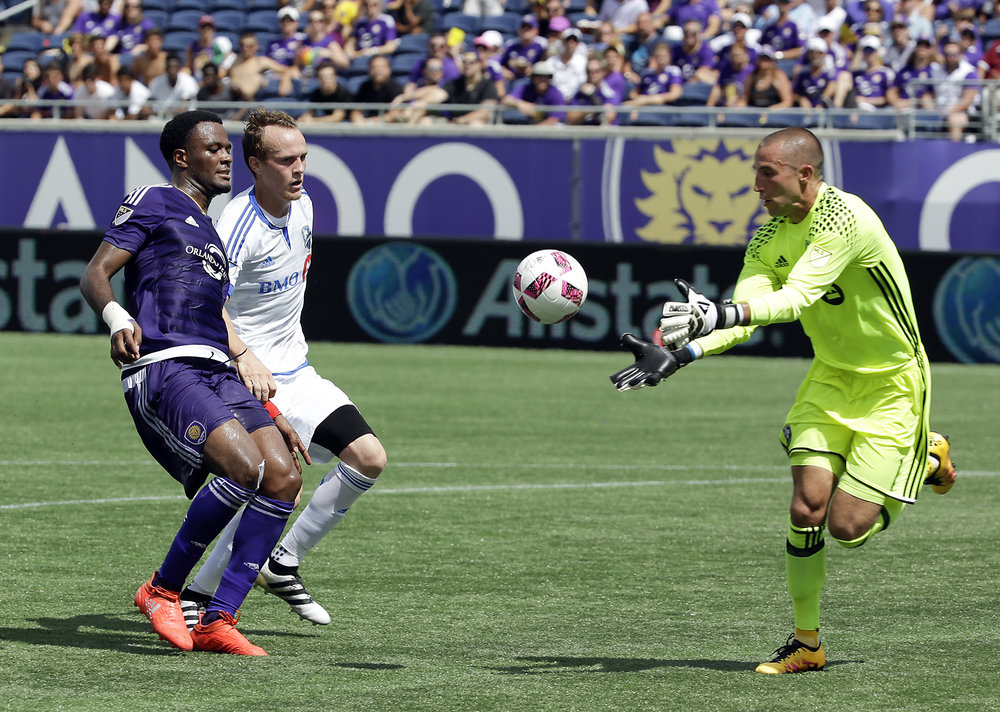 Montreal Impact goalkeeper Evan Bush, right, makes a save in front of teammate midfielder Wandrille Lefevre, center, and Orlando City's Cyle Larin, left, during the first half of an MLS soccer game, Sunday, Oct. 2, 2016, in Orlando, Fla. (John Raoux/AP)