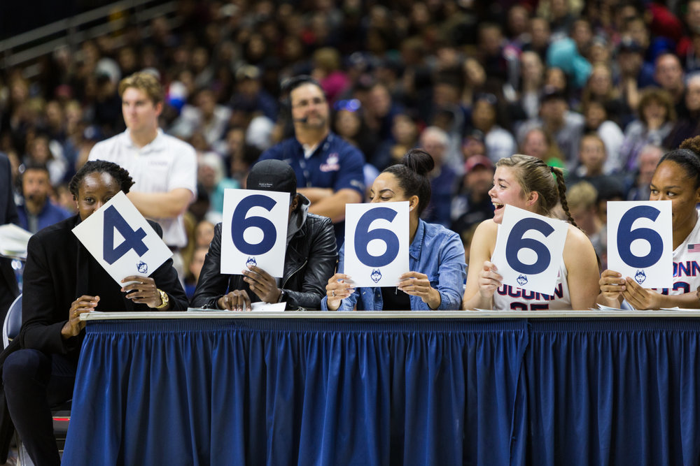 Tina Charles (left) and other UConn women's basketball alumni are joined by current players to judge the dunk contest.