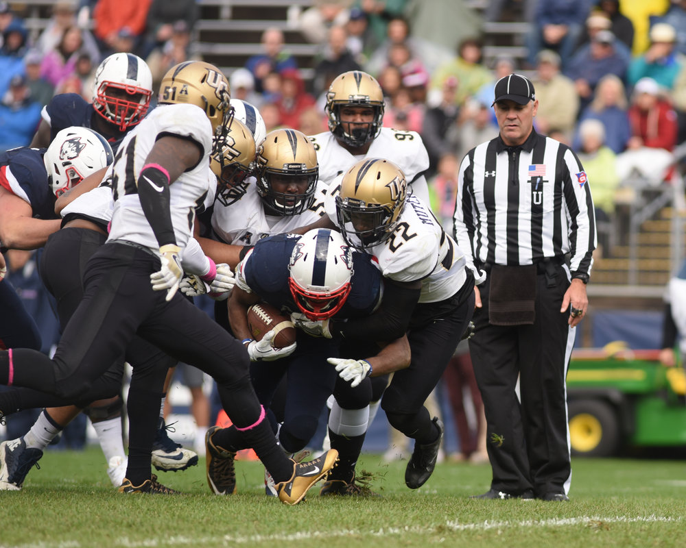 Arkeel Newsome (#22) is blocked by a group of UCF football players. The Huskies lost the homecoming football game to UCF on Saturday, Oct. 22nd at Rentschler Field.(Zhelun Lang/The Daily Campus)