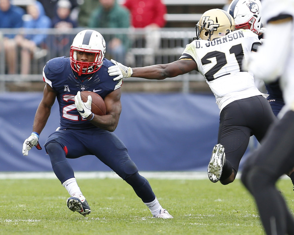 UConn Junior Running Back Arkeel Newsome (22) dodges a tackle from an oncoming UCF defender. (Tyler Benton/The Daily Campus)