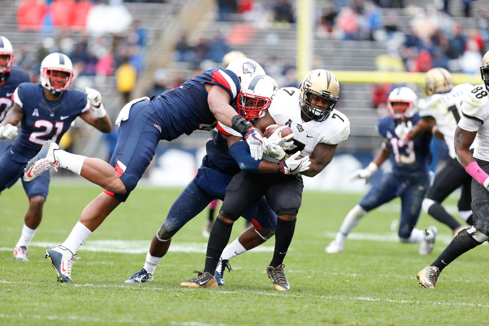 Members of the UConn defensive line tackle UCF running back Dontravious Wilson (7) during the Huskies 24-16 loss to the Knights on Saturday, Oct. 22, 2016 at Rentschler Field. The loss signaled the end of the Civil Conflict. (Tyler Benton/The Daily Campus)