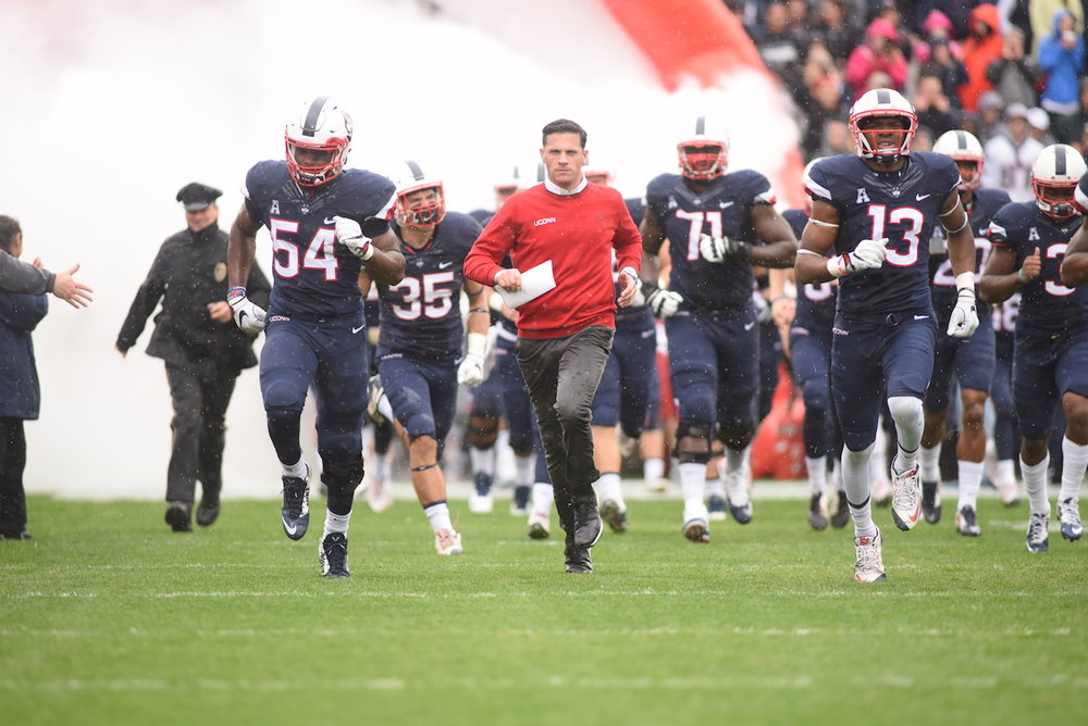 Head coach Bob Diaco runs out of the tunnel alongside senior linebacker Omaine Stephens (#54) and junior linebacker Vontae Diggs (#13) in a game against UCF on Oct. 23, 2016. The Huskies are looking to get back in the win column against ECU this weekend. (Zhelun Lang, The Daily Campus)