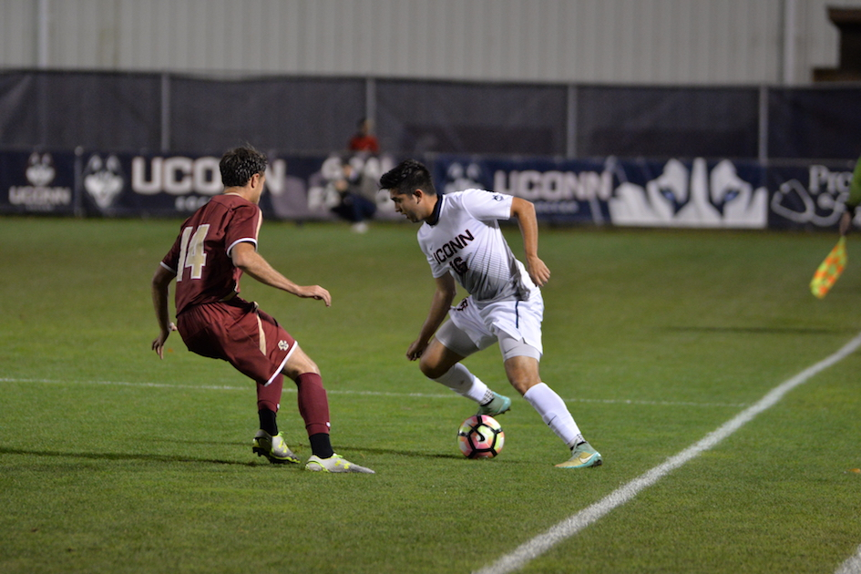 UConn junior midfielder Alex Sanchez (#18) tries to make his way around BC's sophomore defender Abe Bibas (#14) in a game on Oct. 18, 2016. The Huskies won 1-0 in overtime. (Amar Batra/The Daily Campus)
